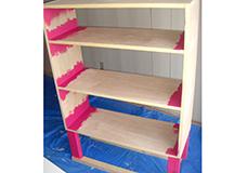10. 塗装をします。塗装用のハケを使い、側板と棚板の接合部や脚など、ローラーで塗りにくい箇所を先に塗っていきます。