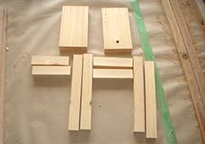 1. キッチンの小さい椅子となるカット済みの材料です。写真上の2枚の板材が座面、縦に置いてある長い角材が脚、横向きの短い角材が横揺れ防止の補強材になります。