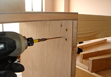 5. 先ほど組み上げたシェルフと脚とをつなげます。脚一本あたりに4本のビスを使い、しっかりと固定します。