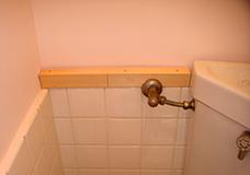 6. 壁面から出ている水洗トイレのタンクへの配水管を目隠しし、さらに小物を置ける棚にしてしまいます。配水管のパーツを避ける形に加工した木材をトイレ壁面に固定します。