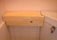 7. 配水管の上面と前面を覆うように木材で囲っていきます。前面に開けてある穴から配水管のネジを回すことができるので、棚をつけたままでの水量の調整が可能になります。