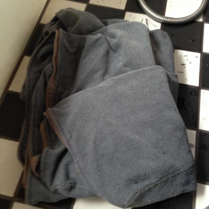 2.次に、衣装ケースに1.5kgの塩を入れ、これまた40度以上のお湯40Lを注ぎ、1で溶かした染料も混ぜてよく混ぜます。この中に染めたい布をたたんで入れて、15分間かきまぜ続けます。こんなに大きい布だと結構大変ですが、色ムラを防ぐためにもがんばりましょう!